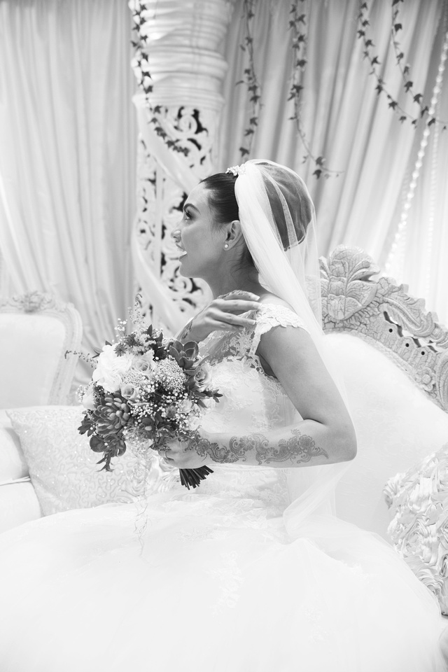 bride at her muslim wedding wearing henna and holing her bouquet of flowers not looking at the photographer